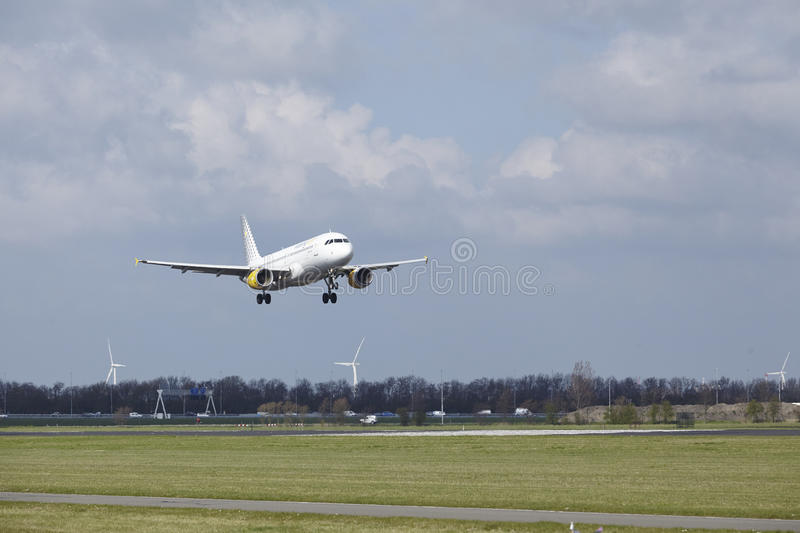 Amsterdam Airport Schiphol - Vueling Airbus A320 lands. The Vueling Airbus A320-216 with identification EC-KHN lands at Amsterdam Airport Schiphol The stock photography