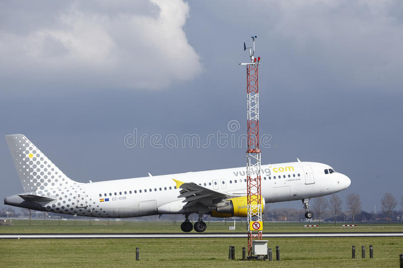 Amsterdam Airport Schiphol - Vueling Airbus A320 lands. The Vueling Airbus A320-216 with identification EC-KHN lands at Amsterdam Airport Schiphol The royalty free stock photos