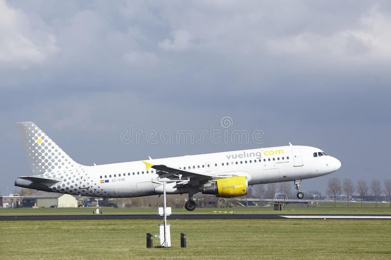Amsterdam Airport Schiphol - Vueling Airbus A320 lands. The Vueling Airbus A320-216 with identification EC-KHN lands at Amsterdam Airport Schiphol The royalty free stock image