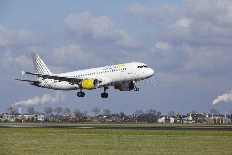 Amsterdam Airport Schiphol - Vueling Airbus A320 lands. The Vueling Airbus A320-214 with identification EC-LOP lands at Amsterdam Airport Schiphol The royalty free stock photos