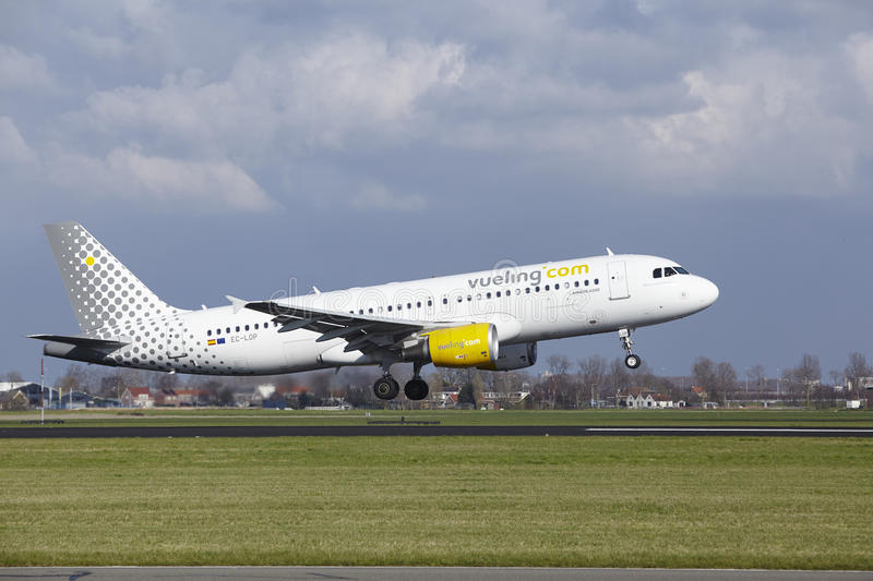 Amsterdam Airport Schiphol - Vueling Airbus A320 lands. The Vueling Airbus A320-214 with identification EC-LOP lands at Amsterdam Airport Schiphol The stock photos