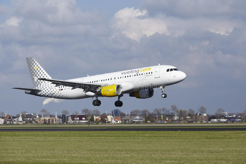 Amsterdam Airport Schiphol - Vueling Airbus A320 lands. The Vueling Airbus A320-214 with identification EC-LOP lands at Amsterdam Airport Schiphol The royalty free stock images