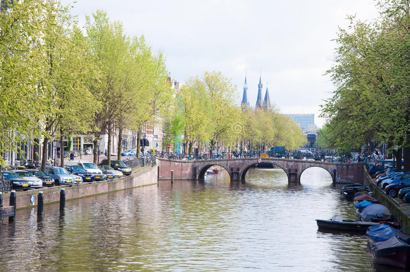 AMSTERDAM-APRIL 30: Amsterdam cityscape with row of cars parked along the canal on April 30,2015, the Netherlands. stock photos