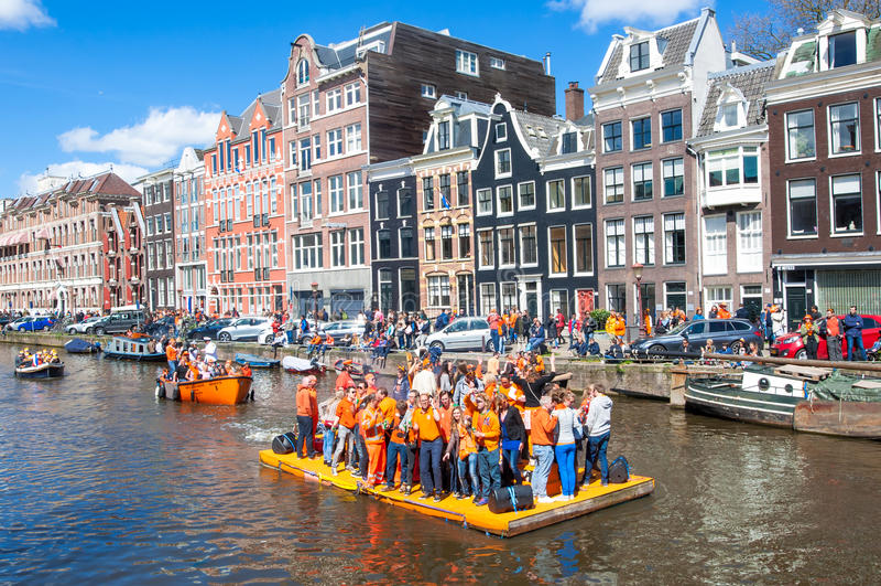 AMSTERDAM-APRIL 27: Det lyckliga folket firar konungens dag längs den Singel kanalen på den orange flotten, folkmassa tycker om f royaltyfri fotografi