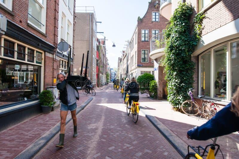 AMSTERDAM-APRIL 30: Jordaan neighbourhood, tourists ride bicycles on April 30,2015. royalty free stock image