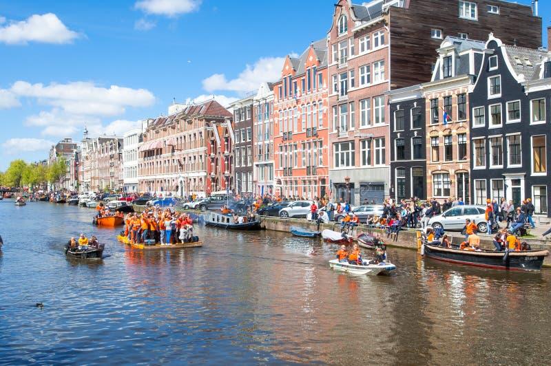 AMSTERDAM-APRIL 27: Szczęśliwi ludzie świętują królewiątko dzień wokoło Amsterdam kanałów, tłum ludzie cieszą się festiwal od ban zdjęcie stock