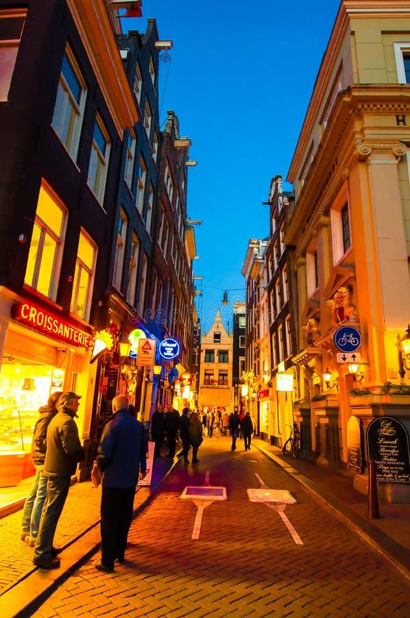 AMSTERDAM-APRIL 27: Uteliv på Amsterdam den smala gatan i rött ljusområde på April 27,2015, Nederländerna arkivfoto