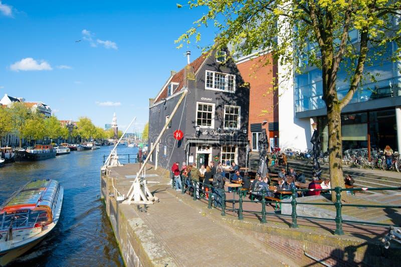 Amsterdam 30 aprile: Cafe de Sluyswacht con la torre di Montelbaans nei precedenti, la gente gode delle bevande aprile 30,2015 fotografie stock libere da diritti