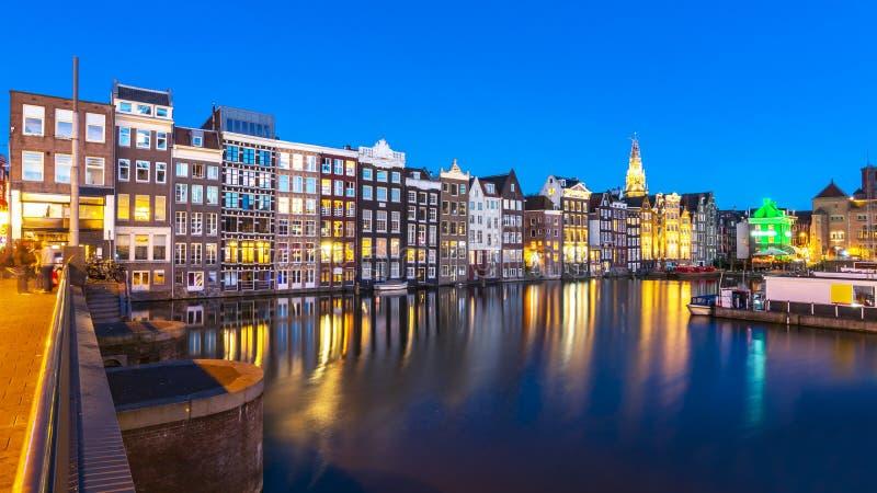 Amsterdam arkitektur längs den Damrak kanalen på natten, Nederländerna arkivbild