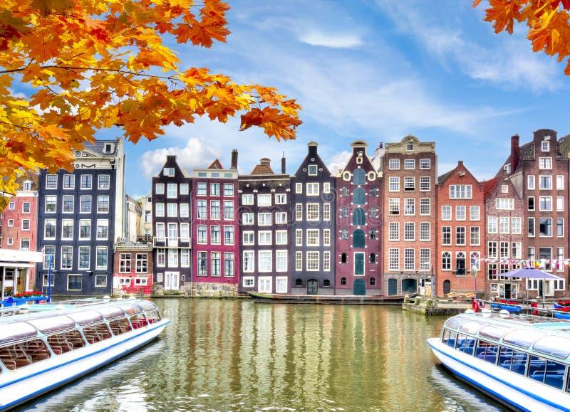 Amsterdam arkitektur på den Damrak kanalen i höst, Nederländerna royaltyfria foton