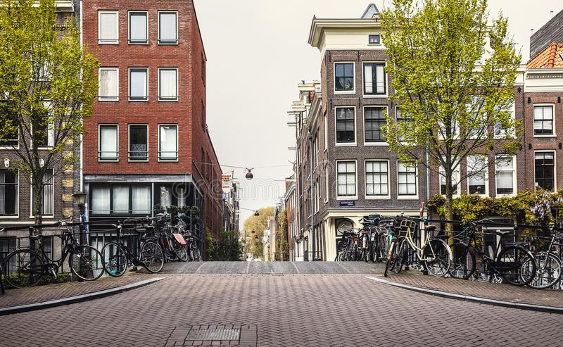 Amsterdam autumn streets with traditional houses urban. Amsterdam. Autumn streets with traditional houses. Urban landscape with bicycles and yellow tree royalty free stock images