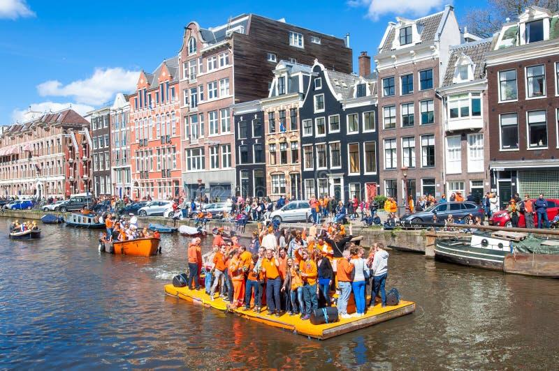 AMSTERDAM 27 AVRIL : Les personnes heureuses célèbrent Day du Roi le long du canal de Singel sur le radeau orange, foule apprécie photographie stock libre de droits