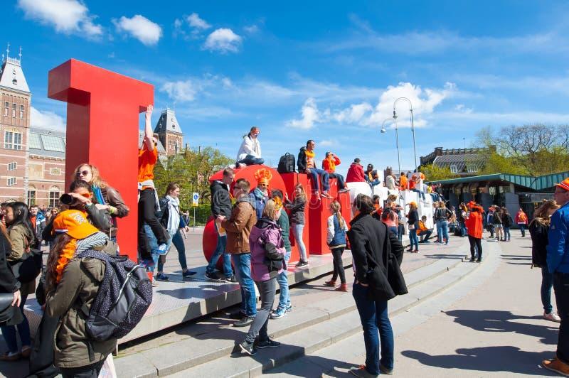 AMSTERDAM 27 AVRIL : Les touristes prennent la photo devant les lettres rouges et de blanc l'amsterdam' d''I photo libre de droits