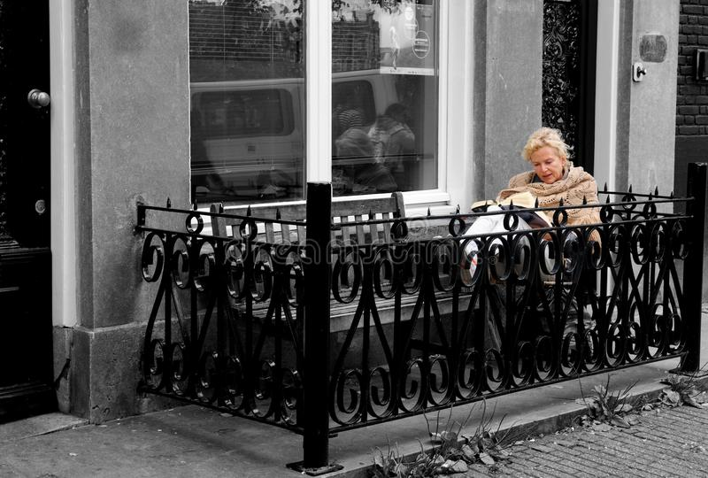 Reading a Book, Street Balcony, Nordic Outdoor Lifestyle, Beautiful Elder Blonde Woman, Amsterdam royalty free stock photography