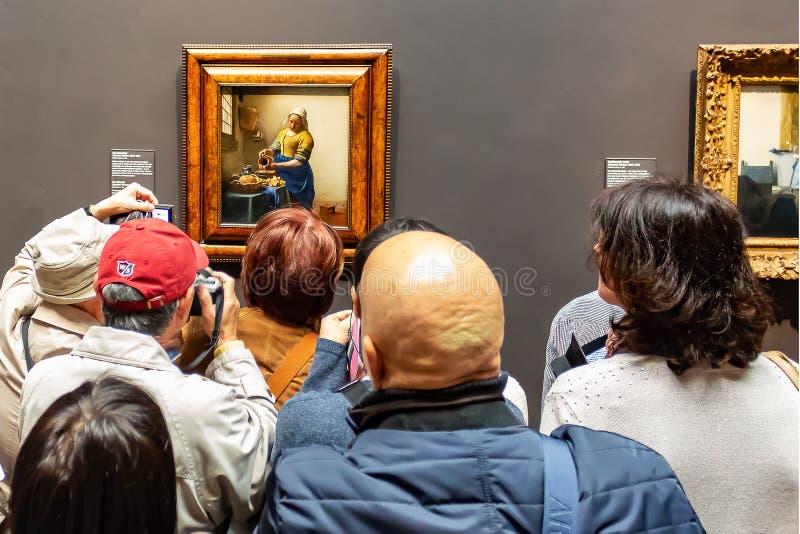 Amsterdam-besökare som ser målningmjölkerskan av Johannes Vermeer arkivbild
