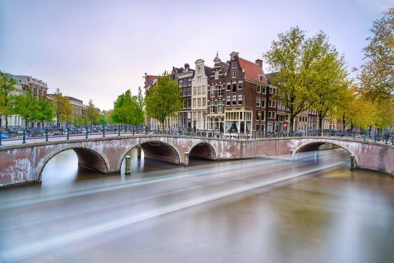 Amsterdam. Bridżowy i wodny kanał. Łodzi światła ślad na zmierzchu. Holandia lub holandie. zdjęcia stock