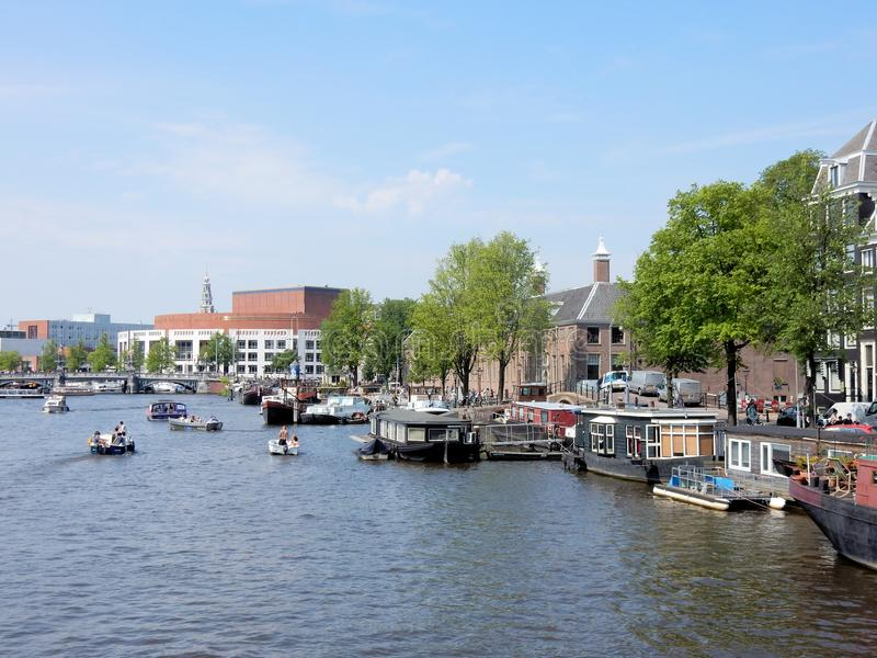 Amsterdam, canal Amstel with Hermitage, Stopera, boats. Amsterdam, canal Amstel with Hermitage - museum , Stopera - city halll, opera, music theater, boats royalty free stock image