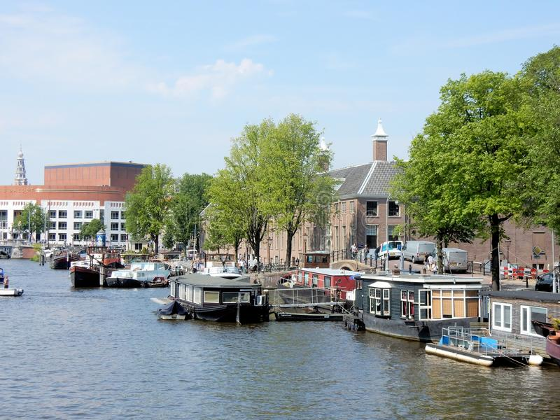 Amsterdam, canal Amstel with Hermitage, Stopera, boats. Amsterdam, canal Amstel with Hermitage - museum , Stopera - city halll, opera, music theater, boats stock photos