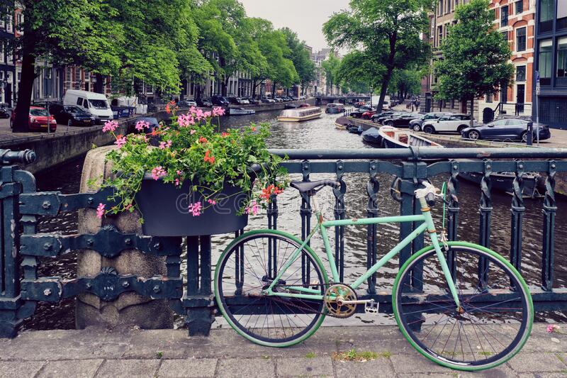 Amsterdam canal with boats and bicycles on a bridge royalty free stock image