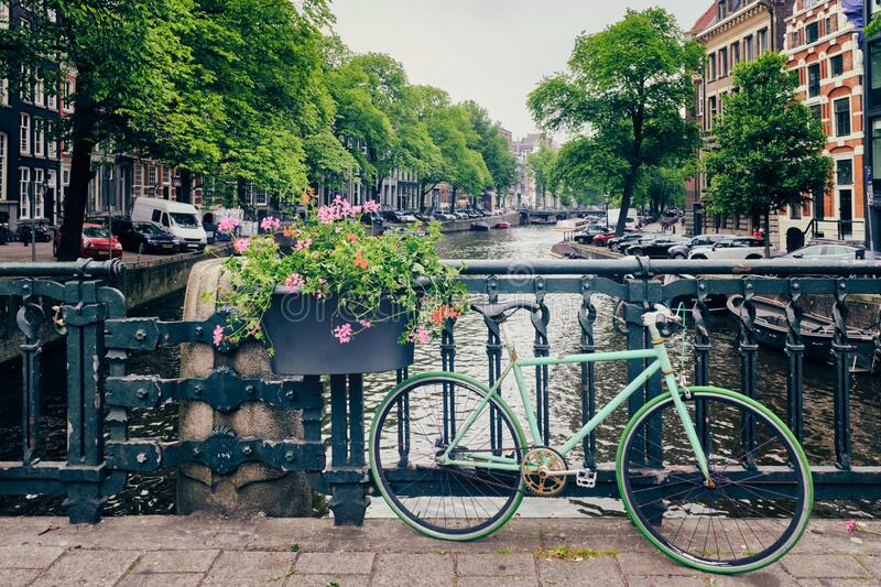Amsterdam canal with boats and bicycles on a bridge stock image