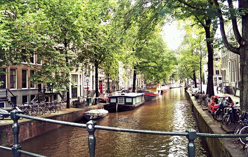 Amsterdam. Canal side at Amsterdam showing house boats and canal boats, netherlands, bicycle stock photo
