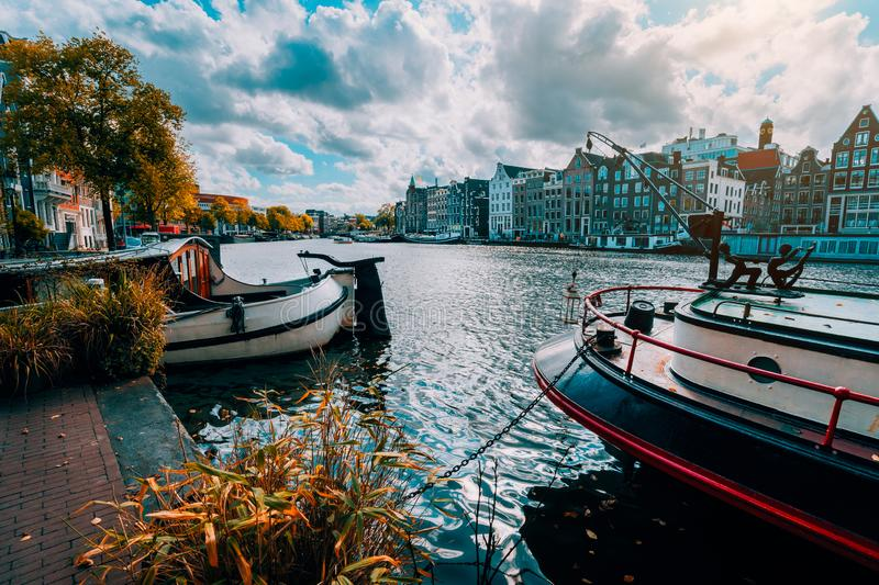 Amsterdam canal Singel with typical dutch houses and houseboats during sunny autumn day. Golden trees and amazing cloudscape. Holland, Netherlands stock images