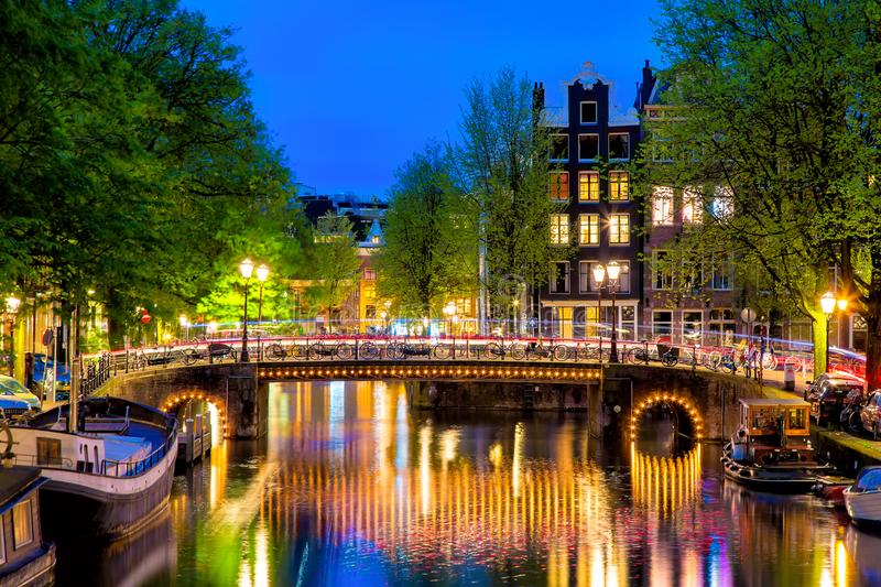 Amsterdam canal with typical dutch houses and bridge during twilight blue hour in Holland, Netherlands. stock image