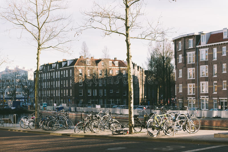 Amsterdam canals in winter. Bycicles parking on a canal in Amsterdam, The Netherlands royalty free stock photo