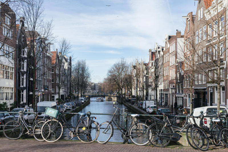 Amsterdam canals in winter. AMSTERDAM, THE NETHERLANDS - 20 JANUARY, 2017: Bycicles parking on a canal. Public transports are expensive and that make bycicles stock image