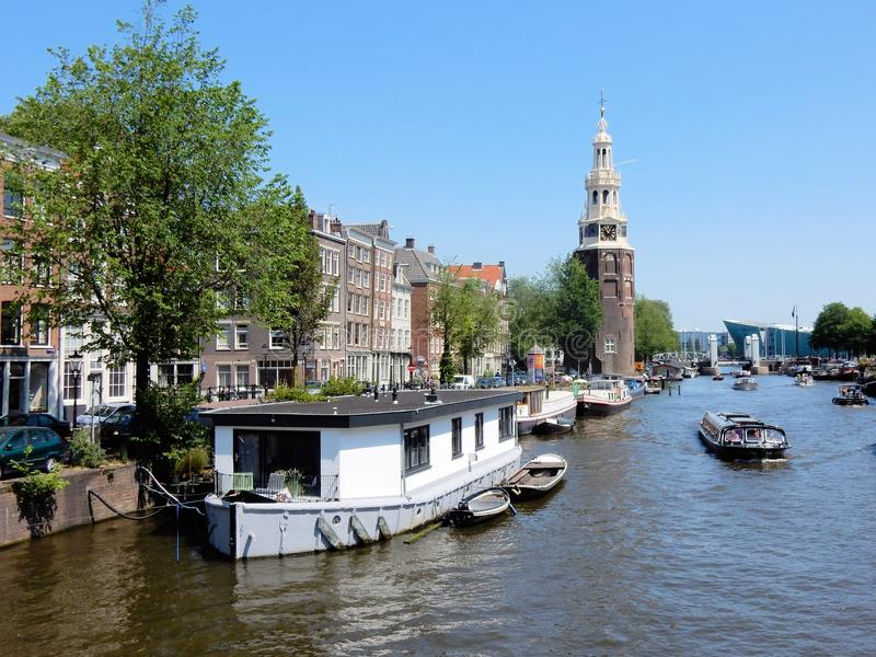 Amsterdam center - canal Oudeschans, canal houses with tower Montelbaanstoren. Amsterdam center - canal Oudeschans with tower Montelbaanstoren, canal houses royalty free stock images