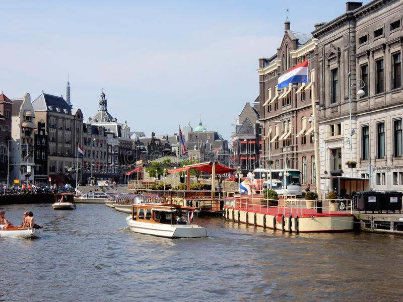 Amsterdam center, canal Rokin with monuments, boats. Amsterdam center, canal Rokin - Oude Turfmarkt with monuments, boats, tour boats on a sunny day - Netherland stock photo