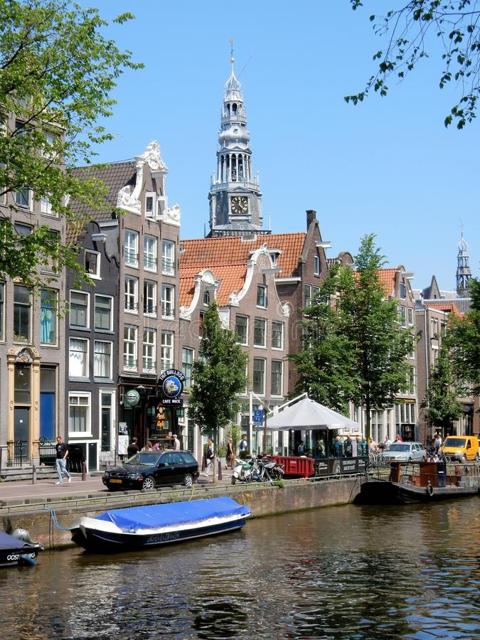 Amsterdam center - Oudezijds Voorburgwal - canal houses with tower Oude Kerk. Amsterdam center - Oudezijds Voorburgwal - canal houses along canal with tower Oude stock image