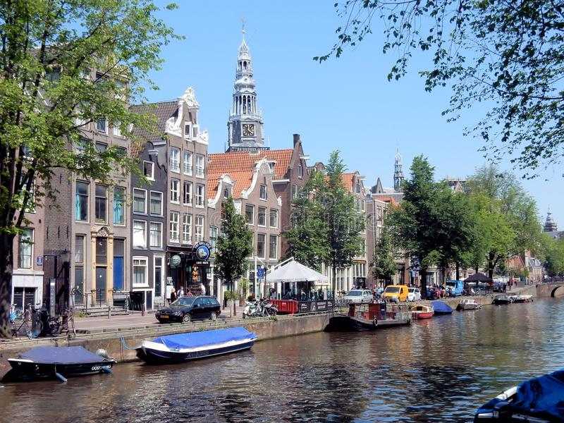 Amsterdam center - Oudezijds Voorburgwal - canal houses with tower Oude Kerk. Amsterdam center - Oudezijds Voorburgwal - canal houses along canal with tower Oude royalty free stock image