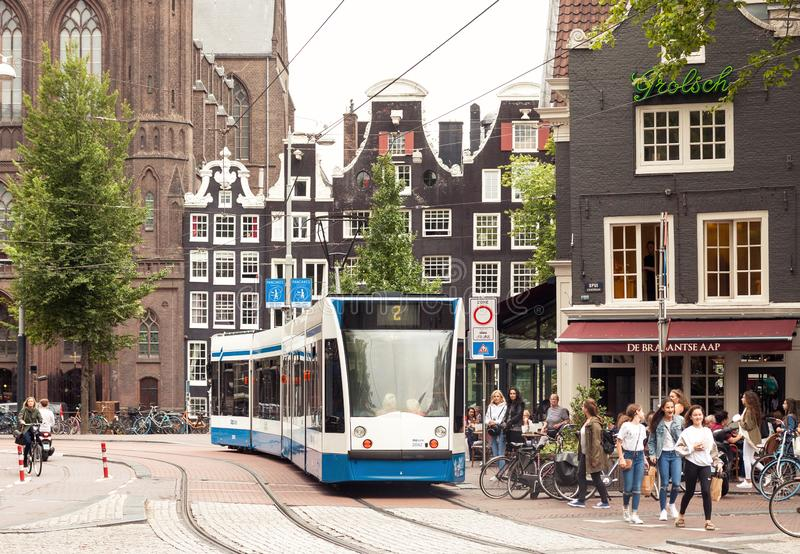 Amsterdam centrum miasta uliczny widok z ludźmi i jawnego transportu tramwajowym omijaniem obok zdjęcia stock