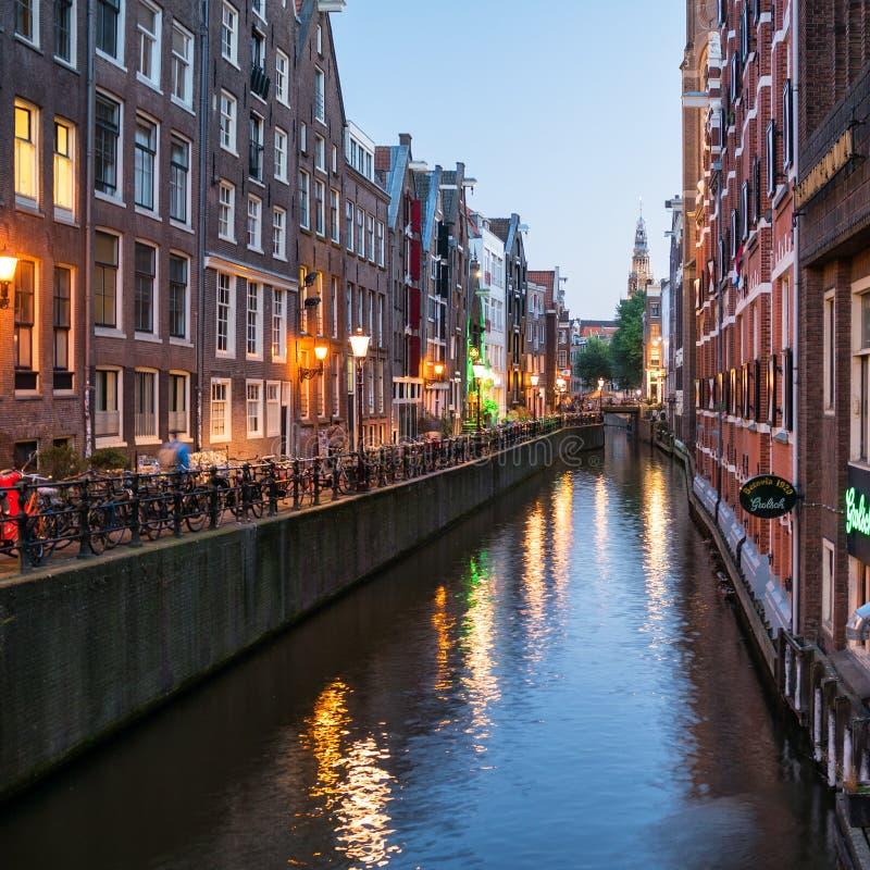 Amsterdam cityscape längs en av cannals och det De Oude Kerk tornet royaltyfria foton