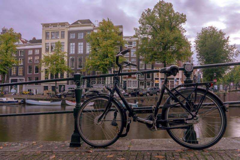 Amsterdam cykel på kanalen arkivfoton