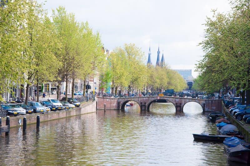 AMSTERDAM 30 DE ABRIL: El paisaje urbano de Amsterdam con la fila de coches parqueó a lo largo del canal en abril 30,2015, los Pa fotos de archivo