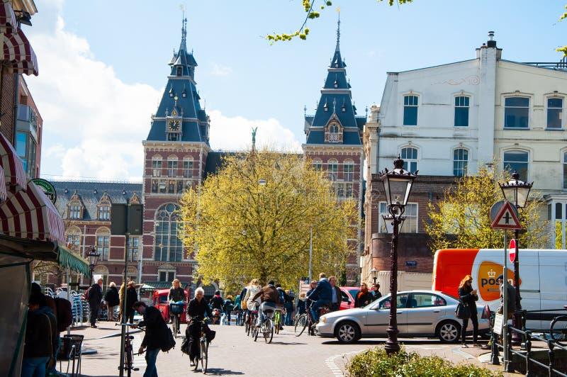 AMSTERDAM 30 DE ABRIL: La gente local monta las bicicletas en la calle de Amsterdam, el Rijksmuseum es visible en el fondo fotografía de archivo