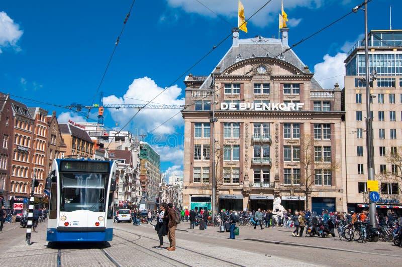 AMSTERDAM 30 DE ABRIL: La tienda principal de De Bijenkorf en el cuadrado de la presa, gente cruza la calle el 30 de abril de 201 foto de archivo libre de regalías