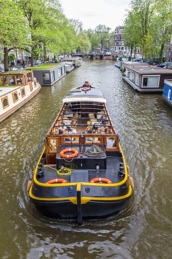 Amsterdam, die Niederlande - 13. August 2017: Kanalkreuzfahrtboot, das Hausboote in Amsterdam führt stockfotos