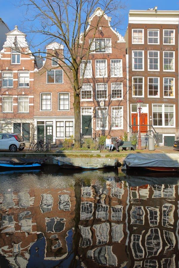 AMSTERDAM, DIE NIEDERLANDE - 23. FEBRUAR 2019: Reflexion von gekrümmten und bunten Erbgebäuden entlang Egelantiersgracht-Kanal stockbilder