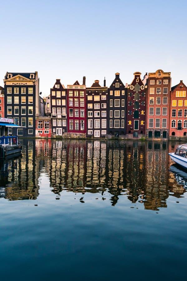 Amsterdam domy z kolorowymi fasadami i pływać statkiem przy Amstel rzeki kanałem łodzie zdjęcie stock
