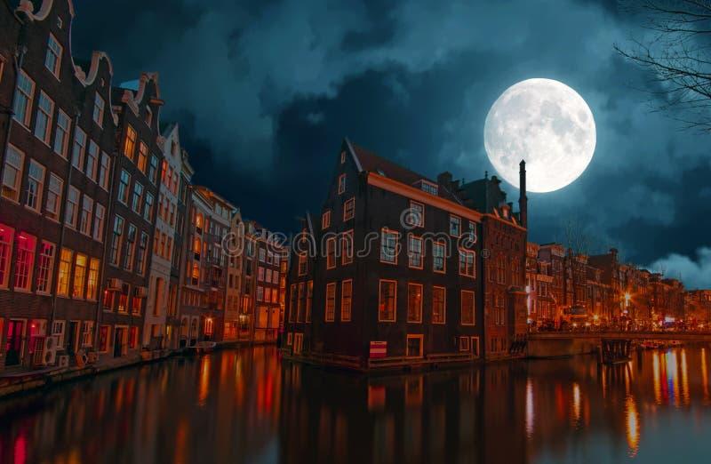 Amsterdam en la noche en los Países Bajos por la Luna Llena foto de archivo