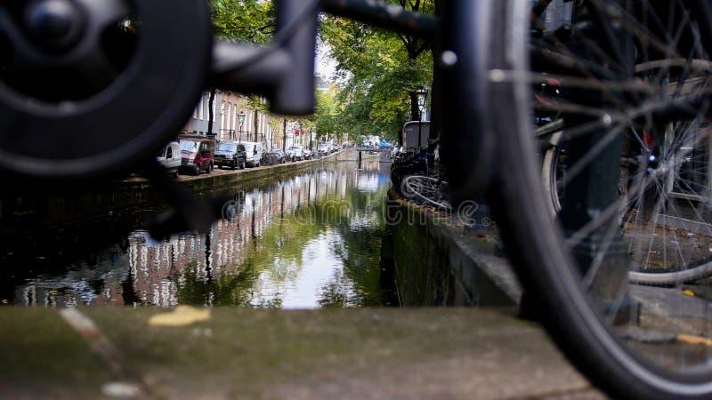Amsterdam gata med cyklar och bilar på kanalen, höst, Nederländerna arkivbild