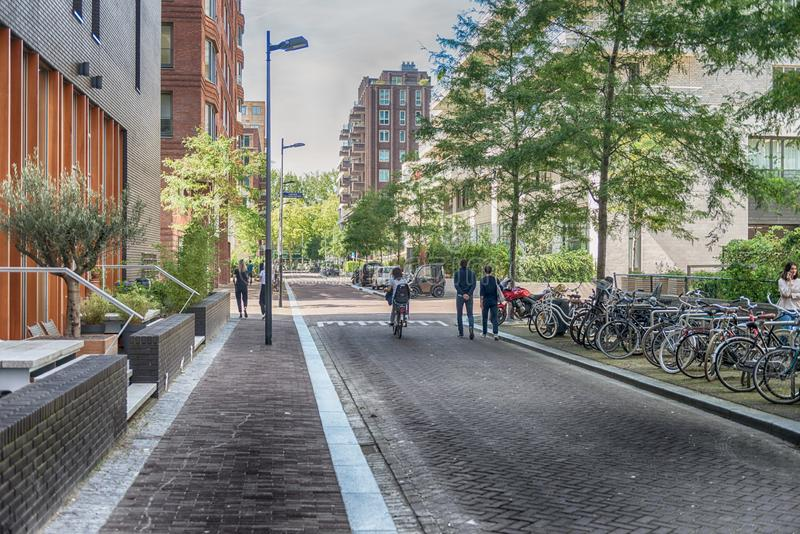 People walking on the streets, luxery apartments at the zuidas in Amsterdam. Amsterdam, George Gershwinlaan, The Netherlands, 08/23/2019, Modern apartments at stock images