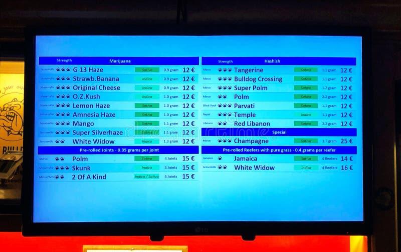 AMSTERDAM, holandie - 20 2018 AUG: Marihuany i haszyszy cennik na dużym ekranie w buldoga coffeeshop wewnątrz obrazy stock