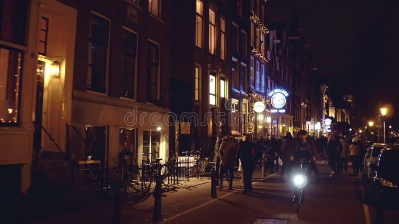 AMSTERDAM, holandie - GRUDZIEŃ 28, 2017 Ludzie chodzą wzdłuż ulicy w wieczór zdjęcie stock