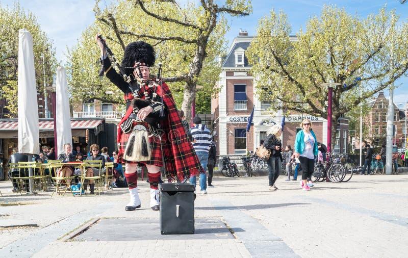 Amsterdam, holandie - Kwiecień 31, 2017: Szkocki bagpiper nastraja jego instrument w ulicach Amsterdam być ubranym zdjęcie royalty free