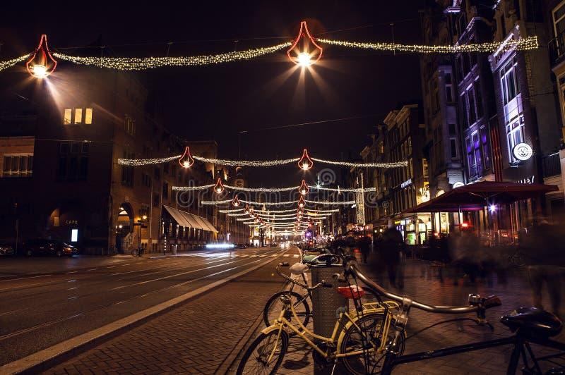 AMSTERDAM, holandie - STYCZEŃ 20, 2016: Nocy ulicy Amsterdam z zamazanymi sylwetkami passersby na Styczniu 20, 2016 wewnątrz obraz stock