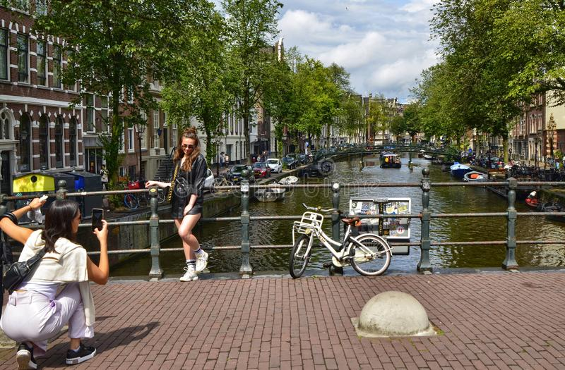 Amsterdam, Holland. August 2019. The bridges on the canals are a must for souvenir photos. A couple of women take a picture: one. Is posed and the other takes stock photography